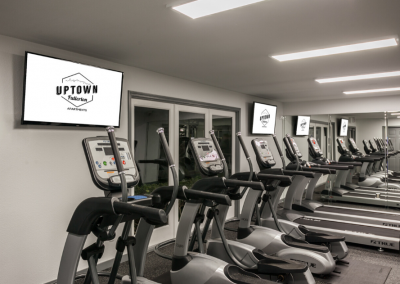 Fitness gym facility with equipment and tvs