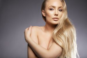 Topless Caucasian female covering breasts with arm