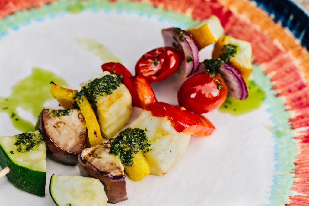 multi color vegetable BBQ skewers with green pesto on white plate