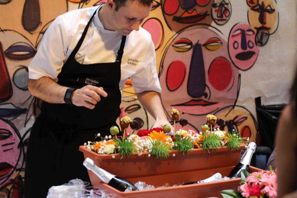 chef tom infront of a wall with faces painted on with colorful food and flowers