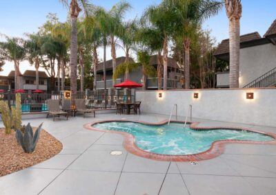 Paved Jacuzzi and Pool with seating and umbrellas