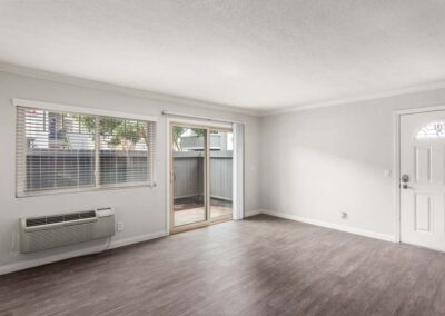 Empty living room with AC unit, windows, and wood-style floors