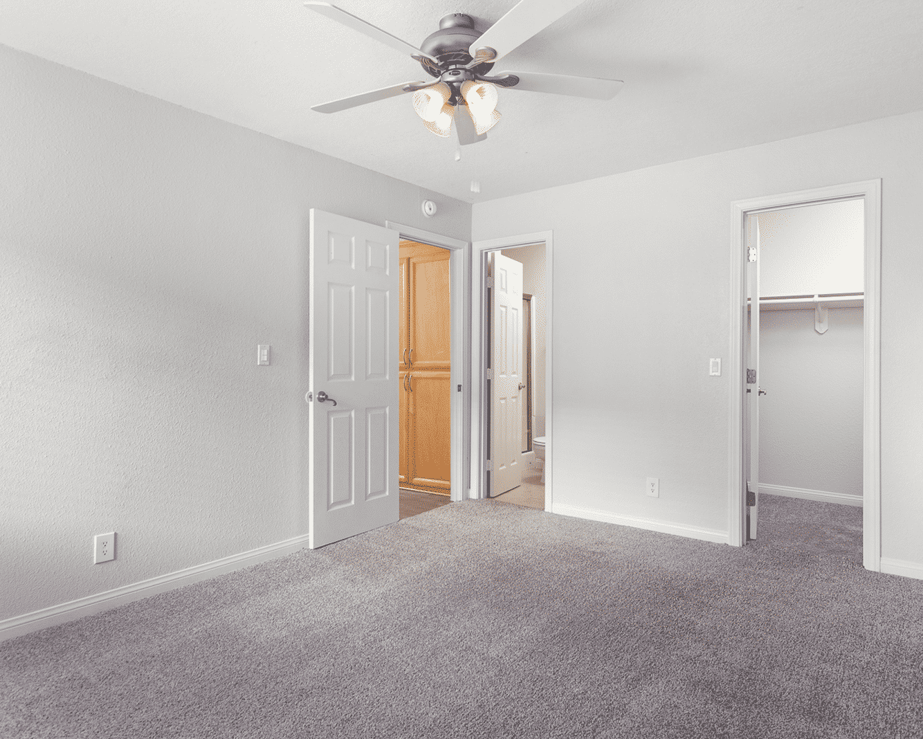 Carpeted bedroom with ceiling fan and big closet space