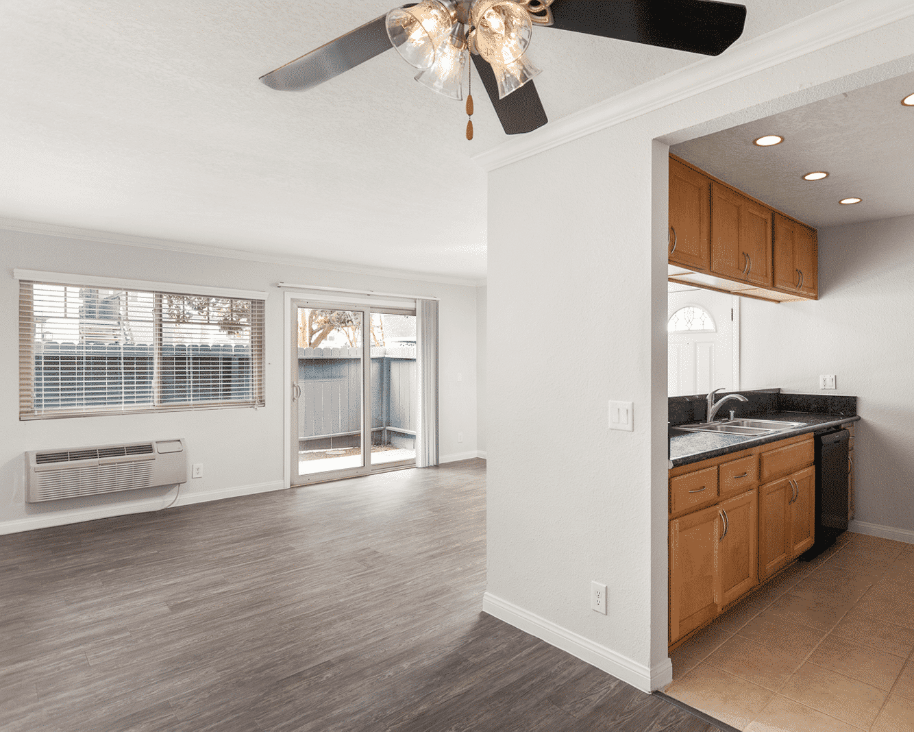 Empty living room with ceiling fan and AC unit and kitchen