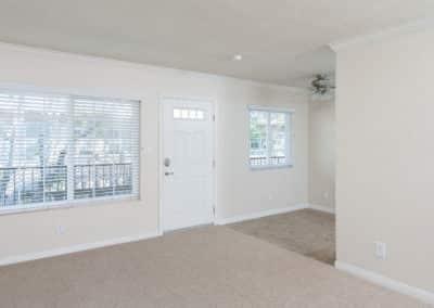 Empty living room with windows and door