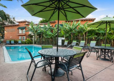 Green umbrella with chairs and tables on the pool area
