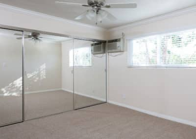 Empty carpeted bedroom with big closet and ceiling fan