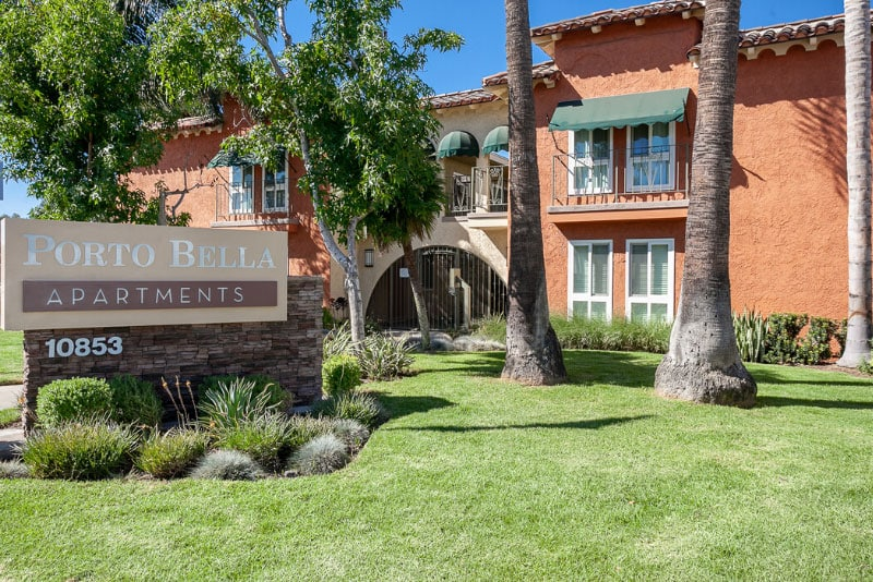 Porto Bella Apartments sign with grass and trees