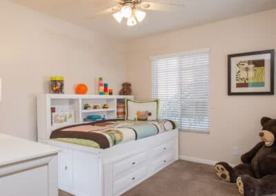 Kids bedroom with ceiling fan and big bear