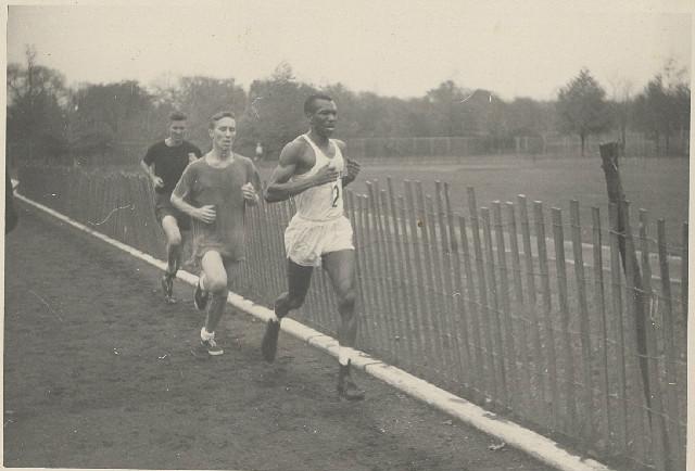 Ted Corbitt Running Near a Wooden Fence