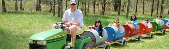 kids on a train being pulled by a John Deere trractor