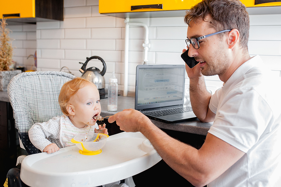Dad working, on the phone, while feeding his baby