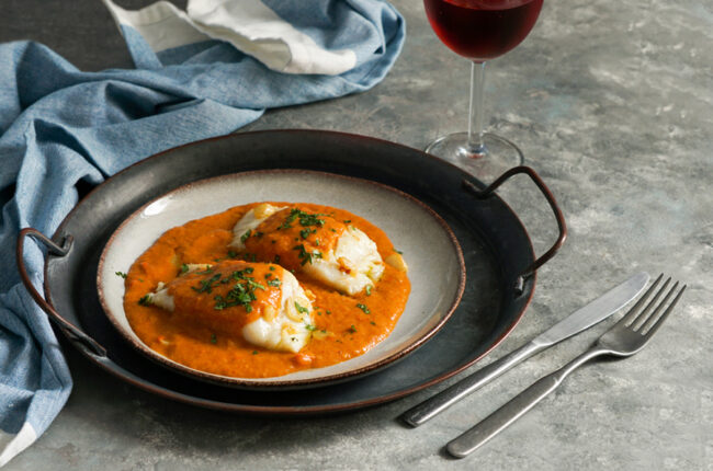 Plate with 2 cod filets in a red pepper sauce