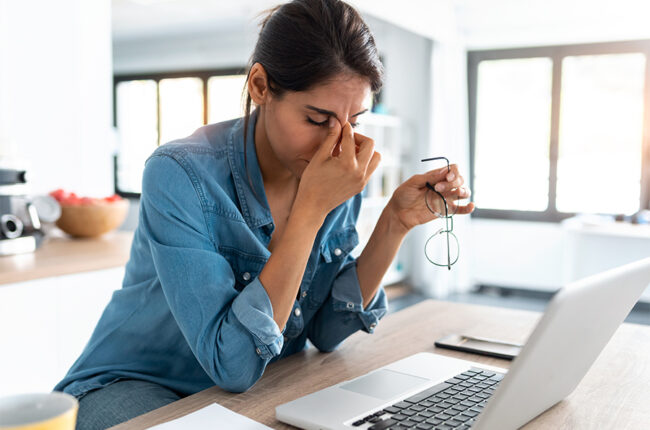 Stressed business woman working from home on laptop looking worried, tired and overwhelmed.