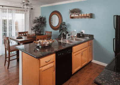View of kitchen cabinets with dining table and windows behind them