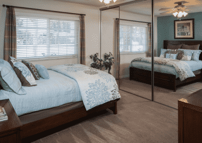 Furnished bedroom with celling fan and mirrors