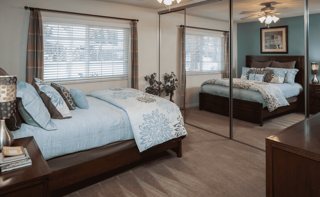 Furnished bedroom interior with mirrors and windows