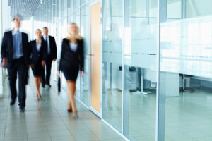 Several business people walking in the glass corridor