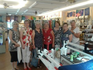 A group of women stand and pose for a photo in a quilting/sewing shop.