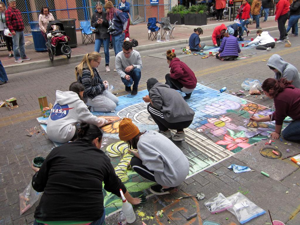 Photo of kids doing chalk art on street