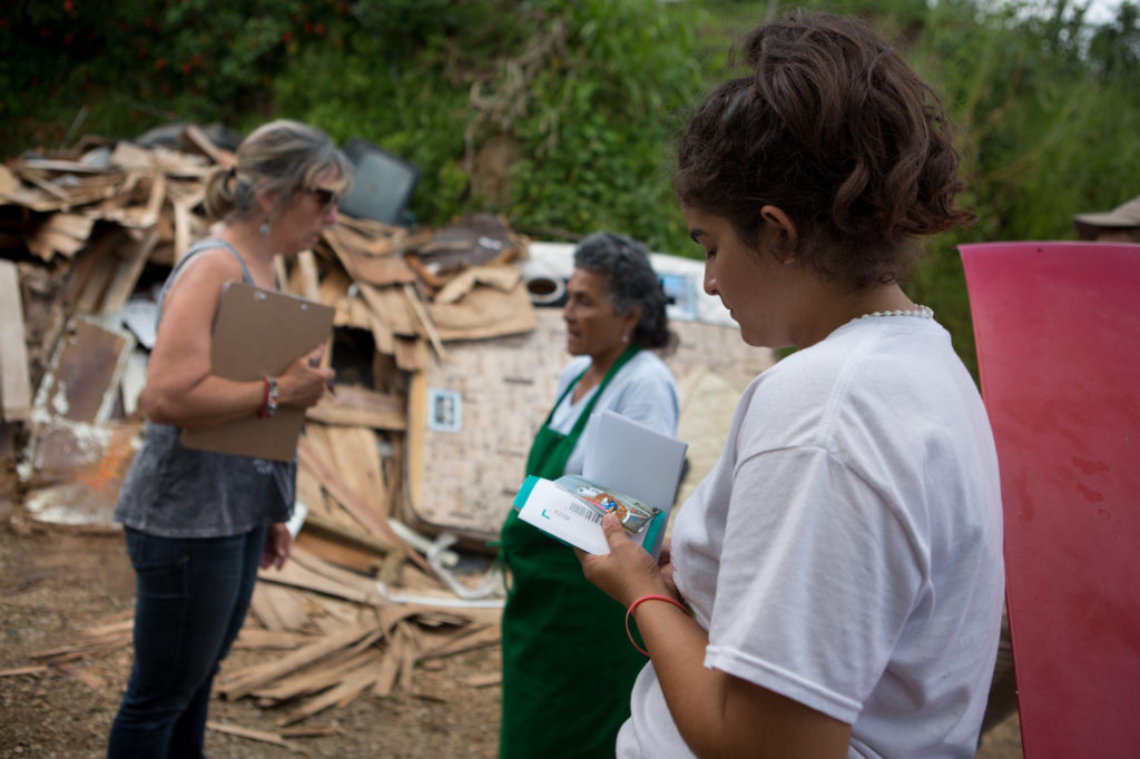 Jumileysie de Jesus de Jesus, 15, looks at photos of her family's damaged home as Silvia XX, left, a volunteer with the local organization Casa Pueblo, which is partnering with LWR in Puerto Rico, speaks to her grandmother Severina de Jesus Hernandez, 74, in front of a pile of ruined belongings dragged from the house after Hurricane Maria inundated the dwelling with water six weeks ago, in the town of Vegas Arriba, in the municipality of Adjuntas, Puerto Rico, November 2, 2017. (photo by Allison Shelley for Lutheran World Relief)