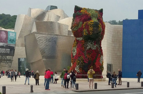 """Entrance to the Guggenheim Museum in Bilbao Spain. """"Puppy"""" flower sculpture by Jeff Koons (1992)."""