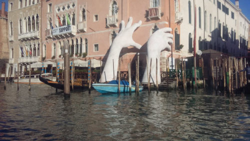 """Lorenzo Quinn's """"Suppport"""" sculpture rising out of the waters of the Grand Canal in Venice."""