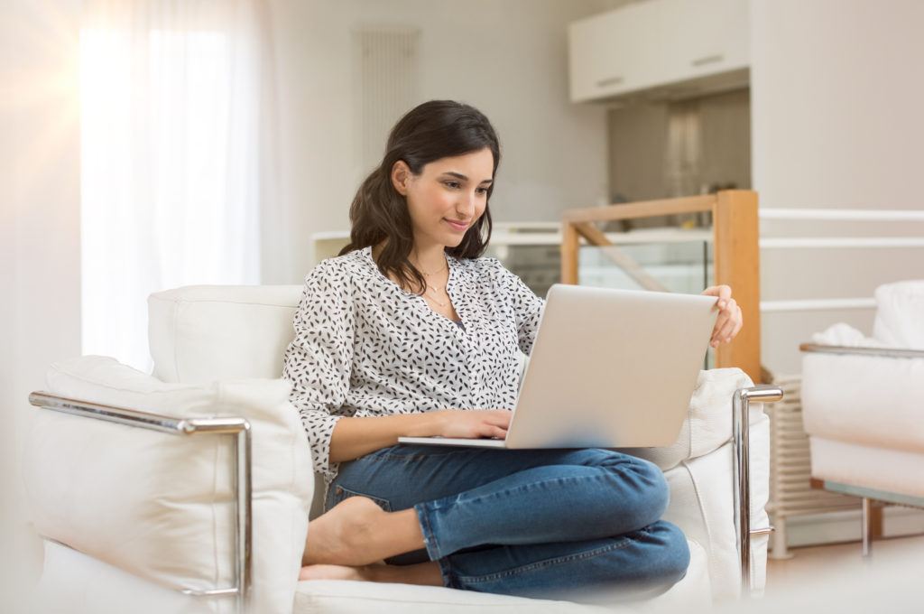 Young woman doing research work for her business. Smiling woman sitting on sofa relaxing while browsing online shopping website. Happy girl browsing through the internet during free time at home.
