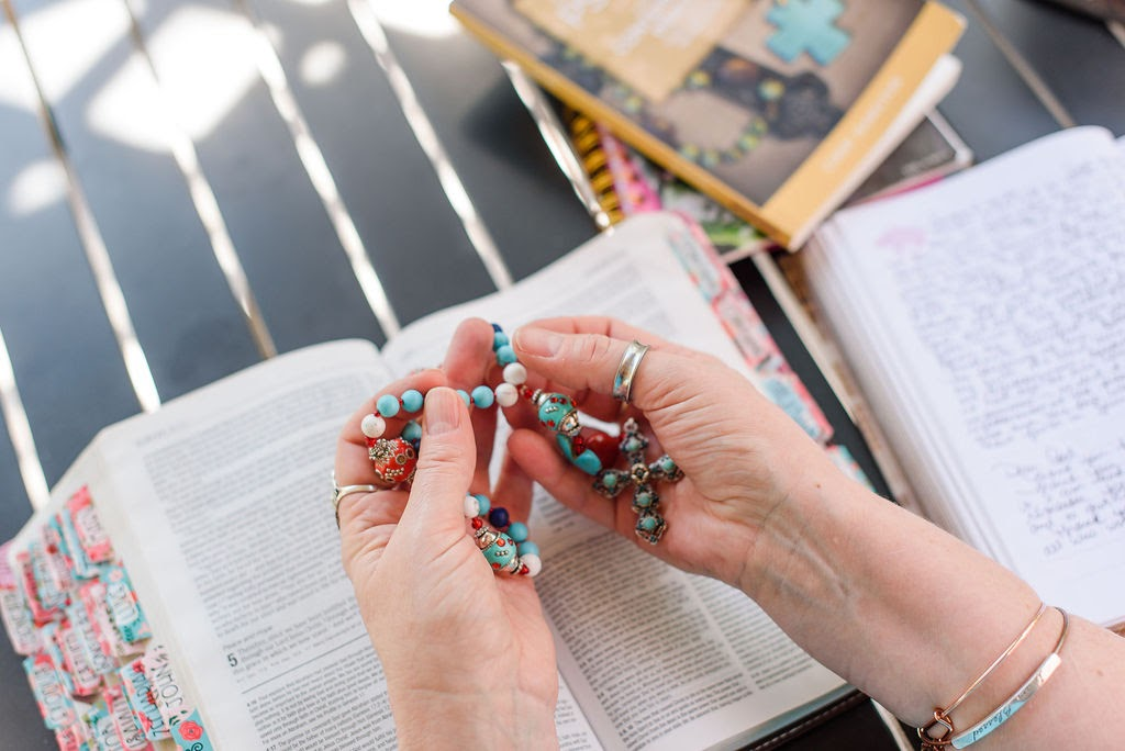 Holding prayer bead jewelry over open Bible