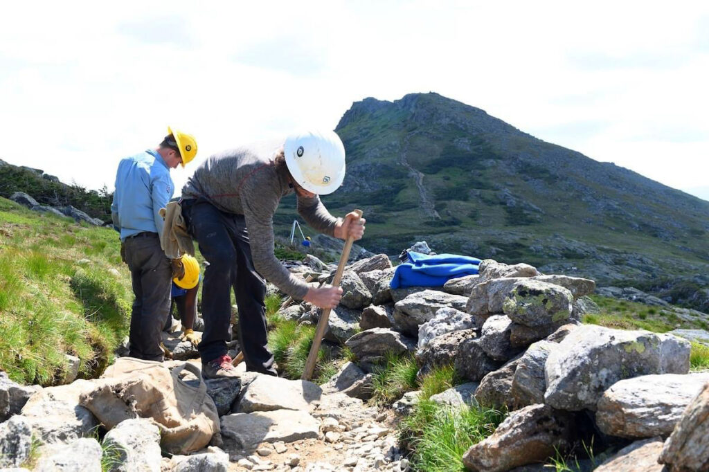 Once the rock makes its way to the project site, crews can start building structures. Here we see a crew member installing some tread stones next to a scree wall.