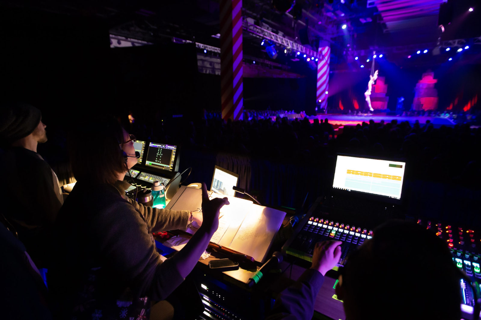 A stage manager has one finger up in standby as acrobat lower to the stage