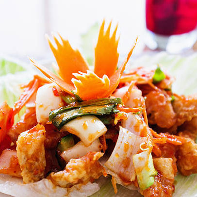 """""""Thai fish salad: crisply fried fish in batter with chilli, spring onions, tomatoes and sweet and sour sauce, all served in a lettuce cup with the classic Thai carved carrot garnish. A glass of grape juice is in the background."""""""