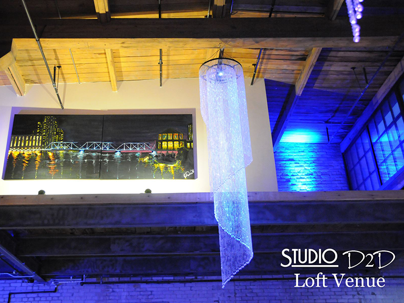 A photo of blue uplighting and a long crystal chandelier at a wedding reception