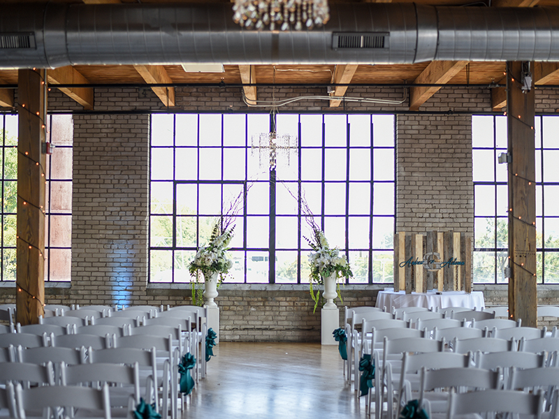 A photo of a ceremony set up in an industrial loft with floral pillars