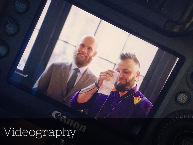 A photo of the back of a camera showing a crying groom at his wedding