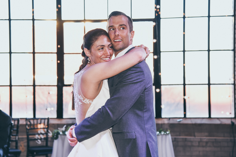 bride and groom dancing in front of a large window looking at the evening skyline