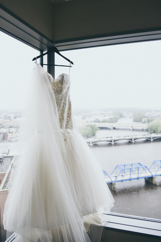 full length photo of a wedding gown and cathedral train hanging in front of a window overlooking Grand Rapids