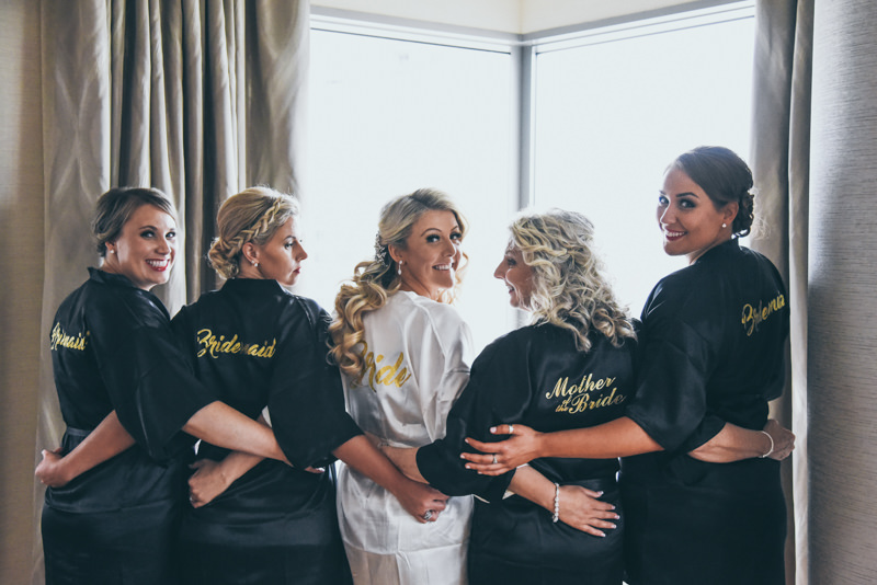 Bride and bridal party in robes looking over their shoulders at the camera