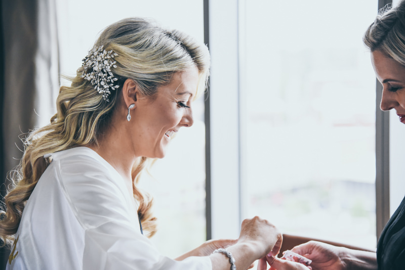 bride putting jewelry on with bridesmaid's help