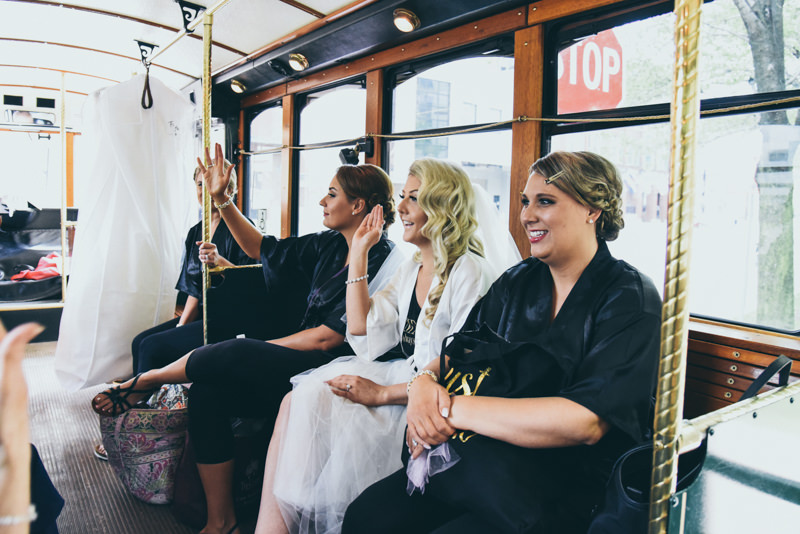 Bride and bridesmaids riding a historic green trolley