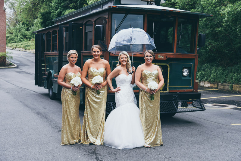 bridesmaids and bride with umbrella in front of historic green trolley