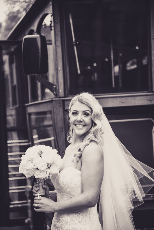 bride holding cathedral veil while standing in front of a green historic trolley
