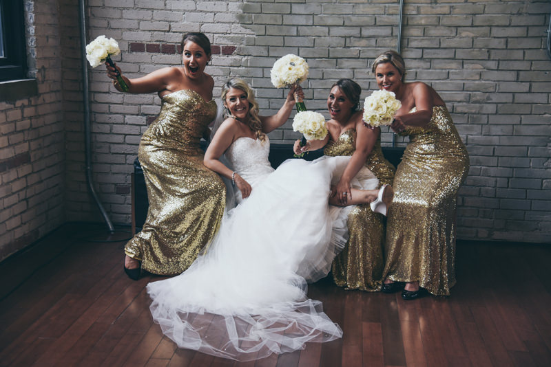 bride and bridesmaids with gold sequin gowns on a black couch in a brick building