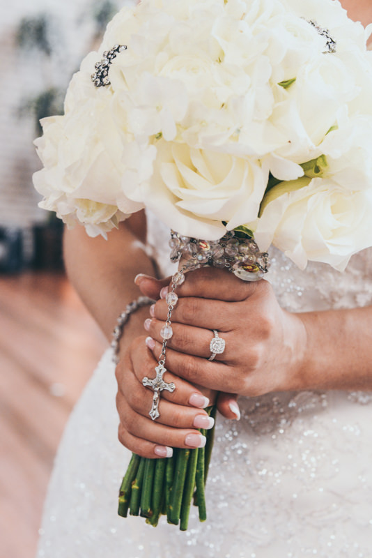 close up of grandmother's rosary wrapped around a bride's bouquet