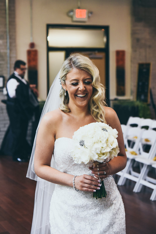 bride laughing as she waits for her father to arrive for First Look