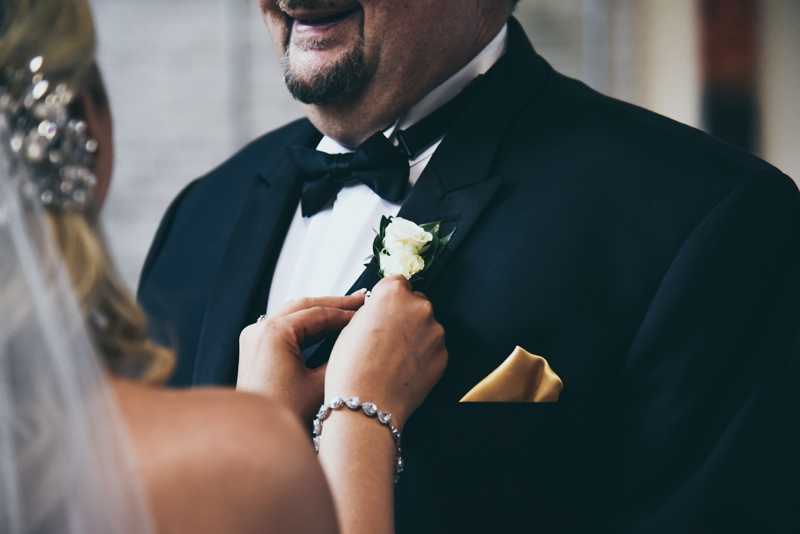 bride pinning father's flower on his jacket at wedding