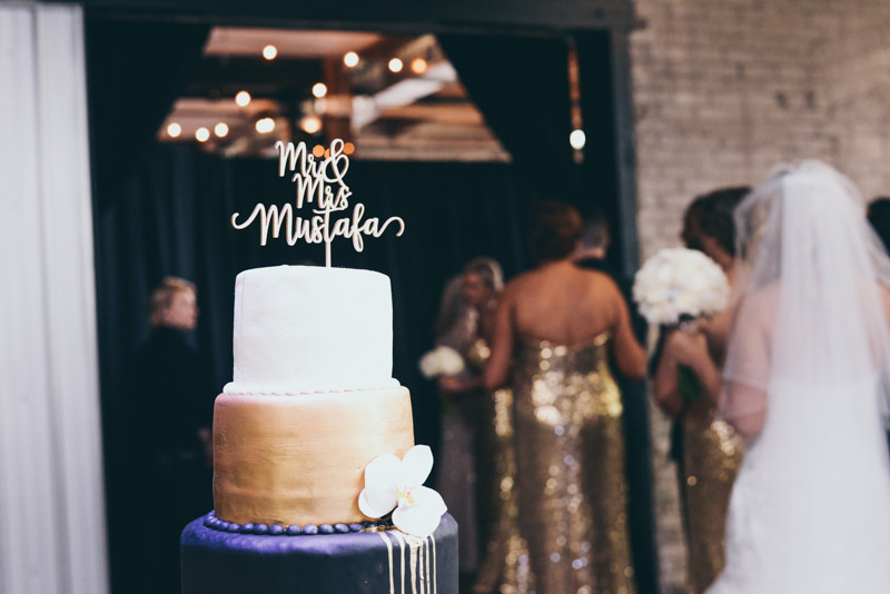Image of wedding cake with bridal party in the back as they prepare to enter wedding ceremony