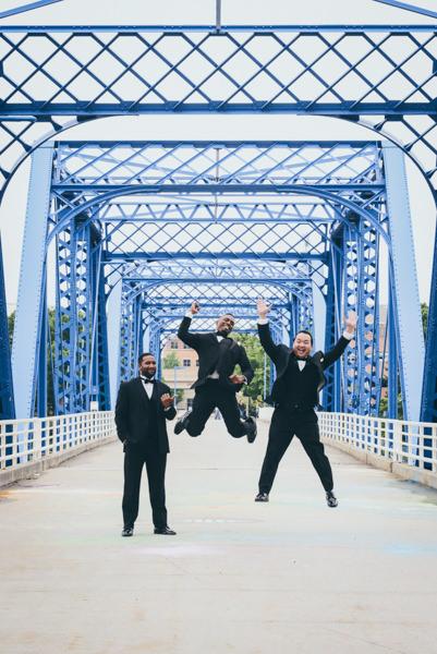 Groom and groomsmen jumping on a historic blue bridge