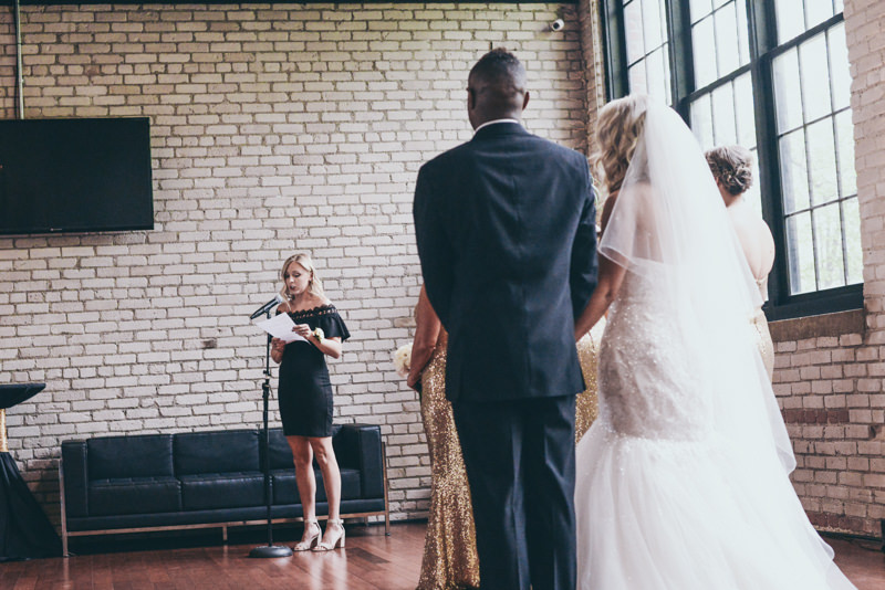 bride and groom from behind as they watch a reader at their ceremony