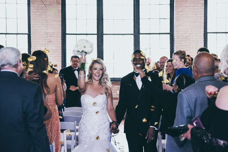 bride and groom walking down the aisle after ceremony while guests throw gold flower petals